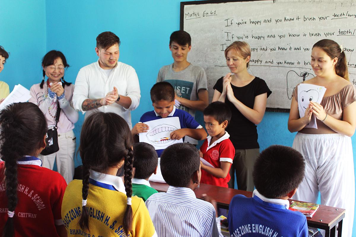 Projects Abroad volunteers teaching in Nepal encourage a student to present to the class in English during a dental hygiene lesson